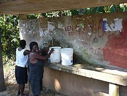 Гаити. Местные женщины перевозят водопроводную<br/> в открытых ведрах.
