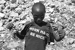 Мальчик-гаитянин позирует<br>с майкой <<Работай усердно. Будь обходителен.>><br>Апрель 2010. Фото Сергея МакКензи